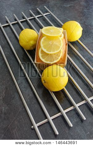 Lemon loaf cake with lemon slices on top and decorated with 3 whole lemons.