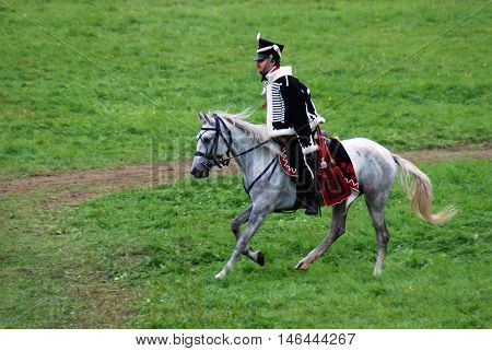 BORODINO MOSCOW REGION - SEPTEMBER 04 2016: Reenactor dressed as Napoleonic war soldier rides a white horse at Borodino battle historical reenactment in Russia. Color photo.