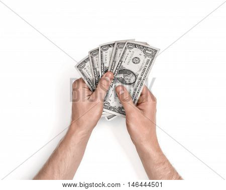 Hands of man holding one-dollar bills on white background. Top view. Economist or an accountant. Home budget. Little cash. Insufficient funds. Counting money.