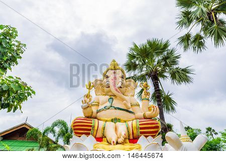 Ganesha Hindu God with plam trees background.