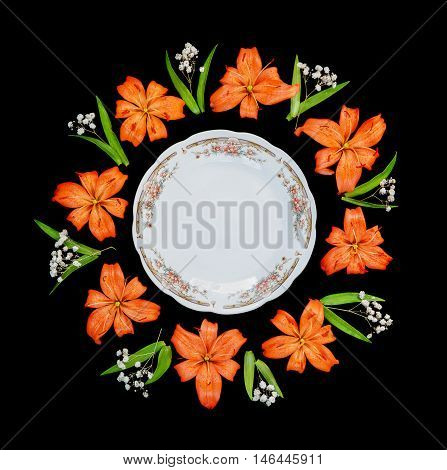 White porcelain empty plate with elegant design surrounded by beautiful orange flowers lilies arranged in the form of a round frame isolated on a black background