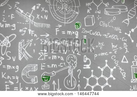 chemical formulas drawn on the gray wall. Laboratory experiments, flasks and jars with the liquid.