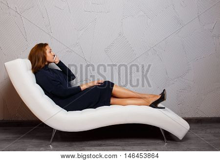 girl talking on the phone sitting on the couch. sad young woman sitting on the couch and talking on the phone. indoors. view profile. empty space for your text.