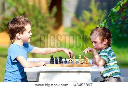 children started the classic a chess match outdoors. two young chess players outdoors. the concept of education