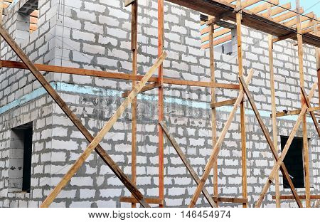 Fragment of wall gray unfinished brick building with wooden scaffolding