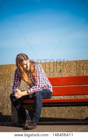 Man bearded long hair wearing plaid shirt casual style relaxing outdoor at summer sunny windy day sitting on bench