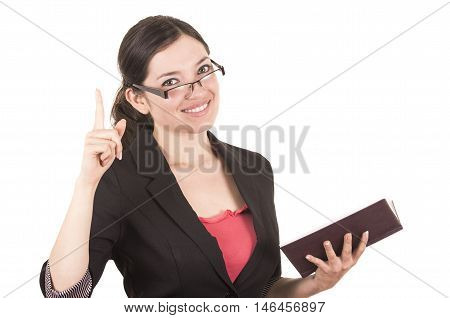 portrait of pretty female teacher wearing glasses and holding book with index finger up isolated on white