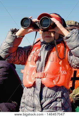 girl in a life jacket looking through binoculars