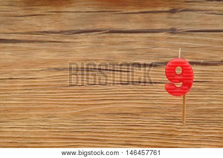 A birth day candle isolated on a wooden background. Red number nine