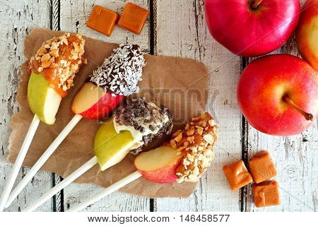 Autumn Apples Slices Dipped With Chocolate And Caramel, Scene On A Rustic White Wood