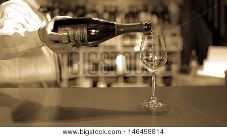 Barman pours fizzy wine in a glass on the bar counter.