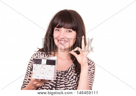 beautiful young happy girl holding present wrapped in a box gesturing all right isolated on white