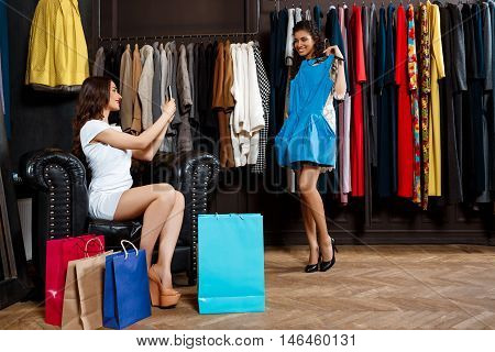 Young beautiful girl taking photo of another trying on dress in shopping mall.