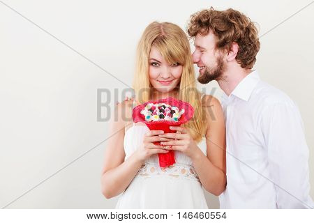 Loving couple with candy bunch bouquet flowers. Man whispering to woman ear sharing secret. Love and flirt concept.