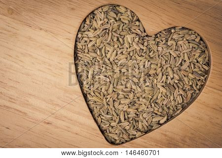 Dried fennel dill seeds heart shaped on wooden surface