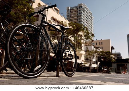 Row of parked vintage bicycles bikes for rent on sidewalk. Bike telaviv Parking In European City. Close up of wheel and bicycle headlight