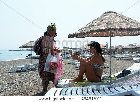 ASSOS, TURKEY - AUGUST 6TH, 2015: Village woman sells her home made knitted product to a tourist on the beach in Assos, Turkey.