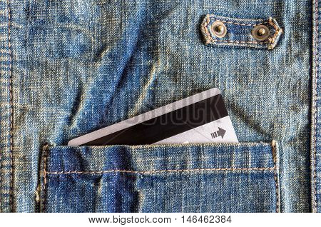 Close-up silver credit card in pocket of denim shirt.
