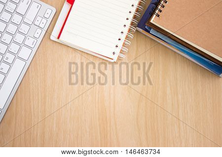 blank paper book on wood table / paper with copy space, keyboard, notebook on a wood desk, view from above / for your text or message / top view