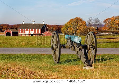 A cannon and a barn on the battlefield at Gettysburg National Military Park Adams County Pennsylvania USA.
