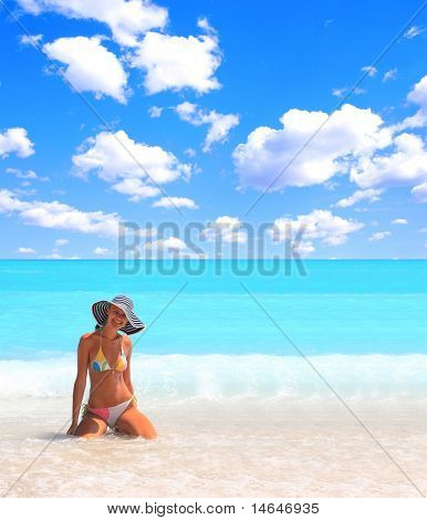 Young beautiful sexy tanned blond woman in bikini in the sea