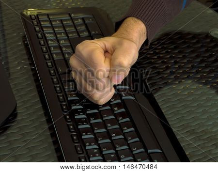 View of an angry man's punch on keyboard