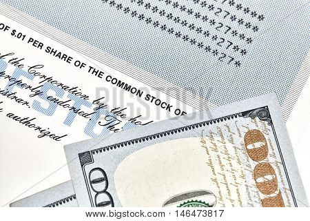 Close up of a stock certificate representing shares in a company with American one hundred dollar bills