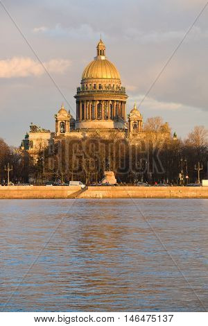 SAINT PETERSBURG, RUSSIA - APRIL 23, 2016: St. Isaac's Cathedral closeup in the rays of the setting sun. View from the Admiralty embankment. Historical landmark of the city Saint Petersburg