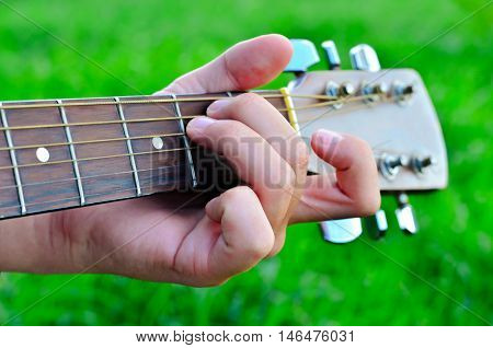 Man's hand and guitar. A man plays the guitar on the background of green grass