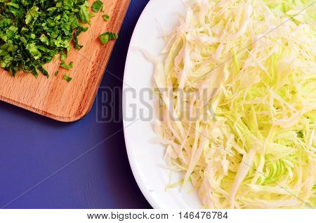 Sliced cabbage in a dish on the table. Chopped parsley and chopped cabbage