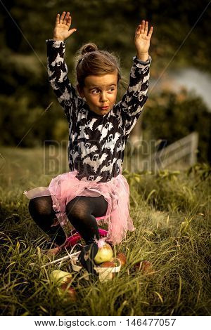 little girl playing on the grass in the daytime, the emotions of a child, a beautiful natural background