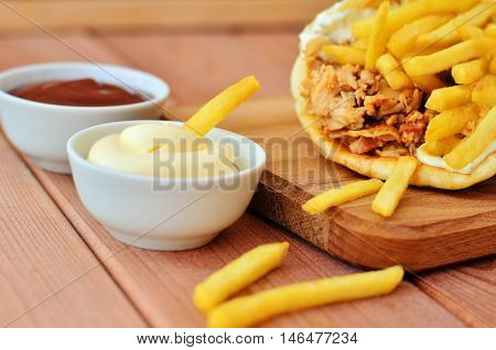 French fries dipped in white sauce. Gyro meat and french fries on a wooden table