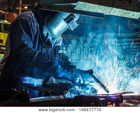 Welder in a steel factory of automotive parts on industry