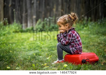 little girl sitting on a red canister, a beautiful background, a sad emotion girl