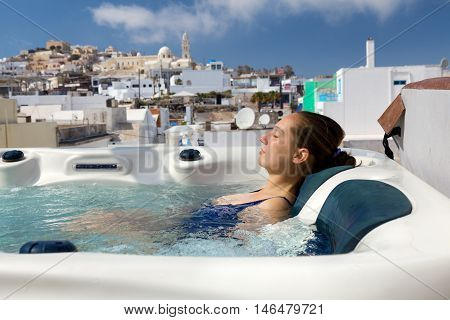 Young woman enjoying outside jacuzzi. In background - the center of Fira Santorini