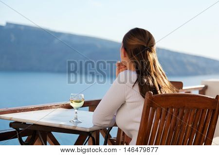 Woman with white wine in Oia Santorini. Looking at the caldera. Horizontal shot