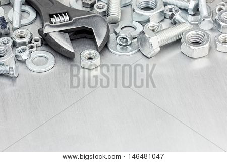 Set Of Screws And Bolts With Adjustable Wrench On Scratched Metal Background