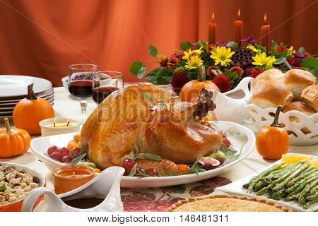 Roasted turkey on a server tray garnished with fresh figs, grape, kumquat, and herbs on fall harvest table. Red wine, side dishes, pie, and gravy. Decorated with mini pumpkins, candles, and flowers.
