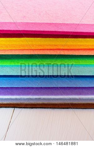 Colored felt sheets on wooden background. Colored felt kit