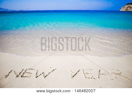 Worlds new year written in the sand of a beach