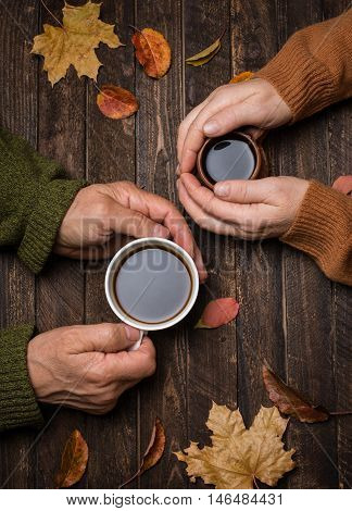 Old people hands. Closeup. The senior people hand holding a cup of coffee on the wood table covered with autumn leaves. Old age concept.