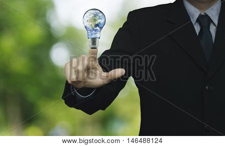 Businessman pressing earth globe in light bulb over blur green tree background Energy conservation and environmental concept Elements of this image furnished by NASA