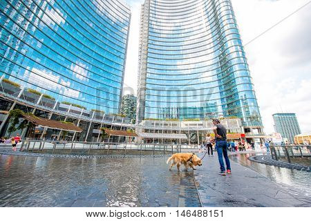 Milan, Italy - June 05, 2016: People walk on Aulenti square with modern skyscrapers on the background in Porta Nuova business district in Milan.