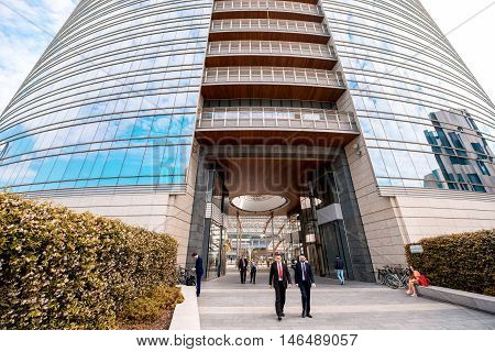 Milan, Italy - June 07, 2016: Two businessmen walk near Unicredit skyscraper on Vincenzo Capelli street in Porta Nuova business district in Milan. It is the main business district in Milan