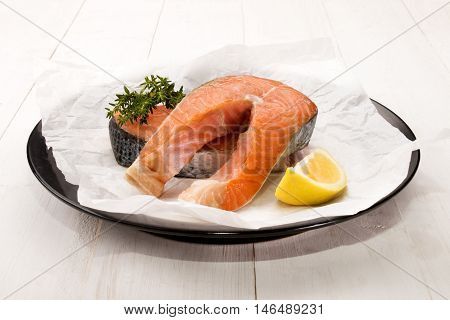 raw salmon steak with thyme and lemon on a plate with white kitchen paper
