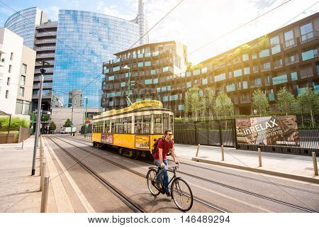 Milan, Italy - June 07, 2016: Modern residantial buildings with old tram and man on the bicycle in Porta Nuova business district in Milan in the morning