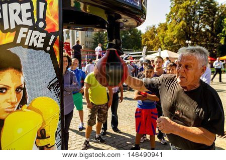Uzhhorod Ukraine - September 9. 2016: Senior man demonstrates the power of his attack on the punching bag of the attraction during the celebration of the Physical Culture and Sports Day. Similar events are held on this day in all cities of Ukraine.