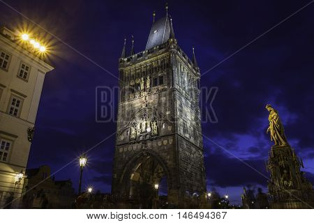 A View from below to the Prague Charles Bridge tower with lights and statue of Charles IV. The tower has reliefs of kingfishers on the surface.