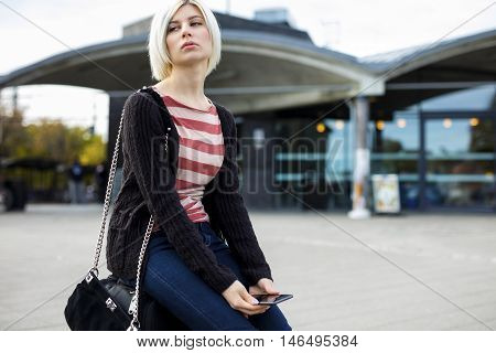 Bored young woman with mobile phone sitting on luggage outside railroad station