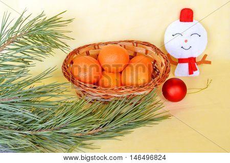 Christmas background. Pine branch, felt snowman ornament, tangerines in the basket